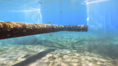 Underwater view of a pipe discharging waste into the sea - 25fps Stock Footage