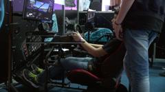 Teenage boy playing car simulator, video game zone, game center Stock Footage