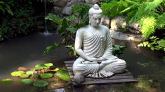 White marble Buddha statue on a pond, water Lilly, exotic place, handheld shot Stock Footage