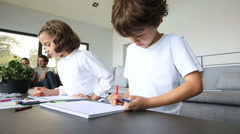 Kids at home drawing, parents in background Stock Footage