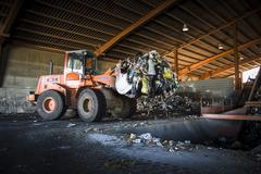 Stock Photo of tractor emptying trash mountains. process of separation of garbage, plastics,