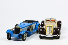 two toy vintage model cars on white - stock photo