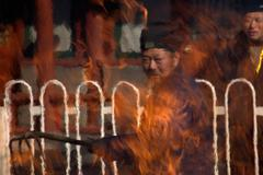 Taoist Monk Tends Fire of Burning Incense Stock Photos
