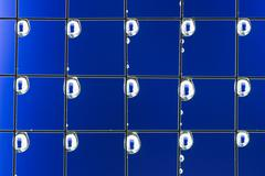 Metal mesh with water drops on the blue background Stock Photos