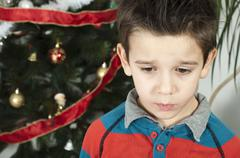 Stock Photo of Unhappy little boy on christmass