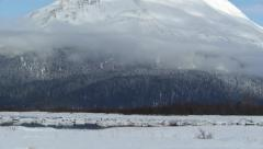 Tilt from Blue and White Sky to Icy River with Snowy Mountain Background - stock footage