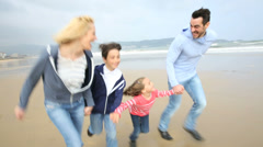 Family running on a sandy beach Stock Footage