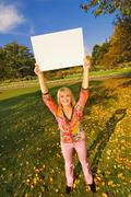 Beautiful girl on autumn background holding a white noticeboard Stock Photos