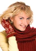beutiful blond girl with blue eyes in winter clothing touching her hair - stock photo