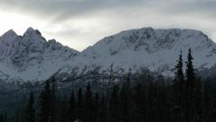 Pan Right Snow Covered Mountain Range with Trees in Foreground Stock Footage