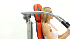 Blonde woman on hydraulic exerciser Stock Footage