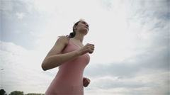 A young woman with a slender figure running at sunset. Slow motion. Stock Footage
