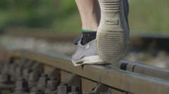 SLOW MOTION CLOSE UP: Walking on railroad track in summer Stock Footage