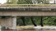 Flood river flowing under the bridge, a man with bicycle standing and watching. Stock Footage