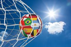 Football in multi national colours at back of net - stock illustration
