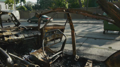 View from explosed and burned car with no roof and side door with a car traffic Stock Footage