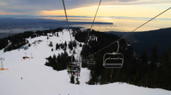 Chairlift going up with snow & vancouver sunset backdrop Stock Footage