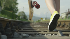SLOW MOTION: Woman walking on railroad holding a longboard Stock Footage