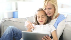 Mother and daughter playing with electronic tablet Stock Footage