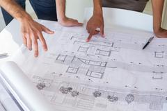 Workers looking at important blueprints - stock photo