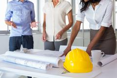 Architects looking at important blueprints - stock photo