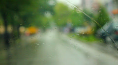 Driving car while raining though town with traffic, shallow DOF Stock Footage