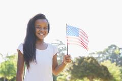 Little girl smiling at camera waving american flag Stock Photos