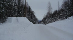 Winter Road, Surrounded by Trees, Cleared Snow Piled on Sides Stock Footage
