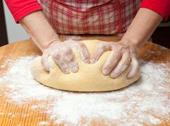 Woman's hands knead dough on wooden table Stock Photos