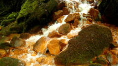 Spring cascades in rapid stream of mineral water. Red ferric sediments Stock Footage