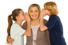 young grandmother with nephew and niece standing on white background - stock photo