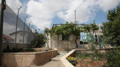 A single Palestinian house completely surrounded by separation barrier  Stock Footage
