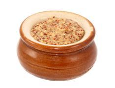 Wholegrain mustard served in a small ceramic pot - stock photo