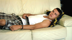 Young attractive teenager boy lying on sofa sleep while watch television at home Stock Footage