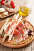 prosciutto ham and grissini bread sticks. italian antipasto - stock photo