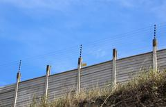 Electric security fence atop a precast wall Stock Photos