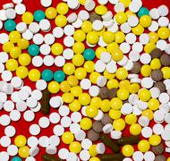 Pile of different pills on a red fabric background Stock Photos