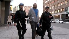 4K UHD - Riot police walking with a protester in handcuffs Stock Footage