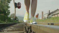 SLOW MOTION: Young woman walking on railroad track Stock Footage