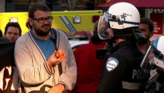 4K Protester tease riot cop by offering an apple Stock Footage
