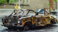 Burned car on road with car traffic on a background timelapse Stock Footage