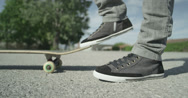 Stock Video Footage of SLOW MOTION CLOSE UP: Skateboarder picking up his skate