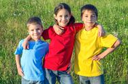 Stock Photo of three smiling kids on the meadow