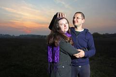 couple is goofing around at sunset - stock photo