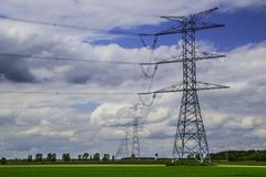 High voltage pylons, electric lines, blues sky, green field - stock photo