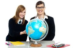 Teacher and student viewing globe in geography classroom Stock Photos