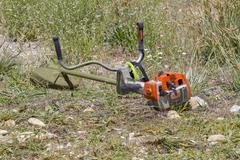 brush cutter, cutting weeds in a garden - stock photo