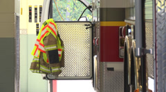 Firetruck with gear hanging on open door Stock Footage
