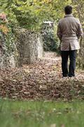 man walking on fallen leafs - stock photo