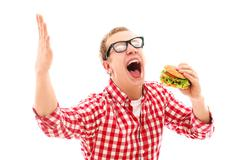 Funny man in glasses eating hamburger - stock photo